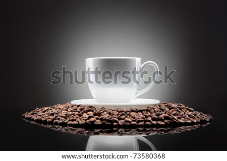 white cup with coffee beans on black - stock photo