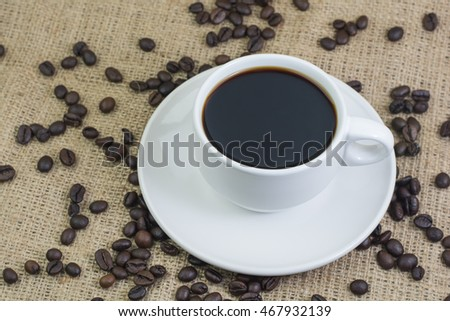 White cup with coffee drink on jute bag background