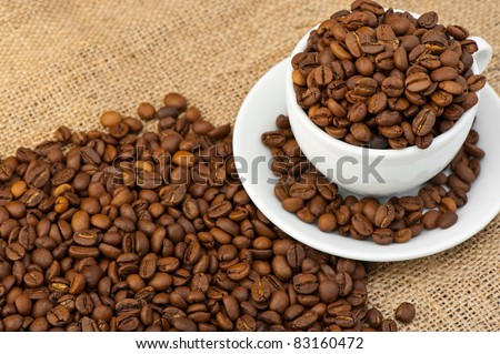 White cup with coffee grains. Grunge background