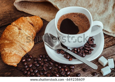 White Cup With Coffee On A Saucer On A Wooden Table