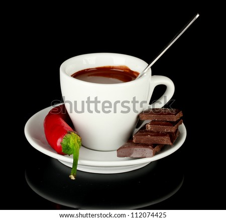 white cup with hot chocolate and chili pepper isolated on black - stock photo