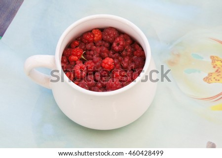White cup with raspberry