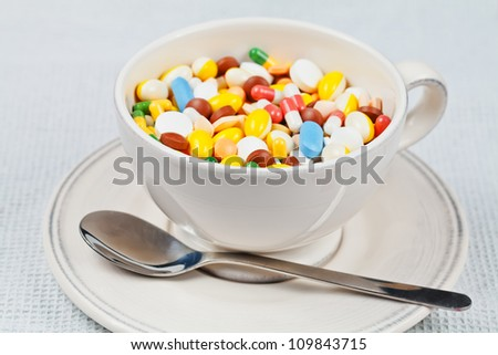 White cup with spoon on the plate filled with white, red, green, brown, blue and yellow medicine pills and capsules served as breakfast - stock photo