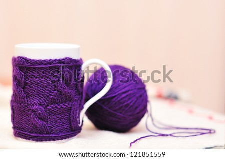 White cup with violet knitted dressing on and knitted ball with beige background - stock photo