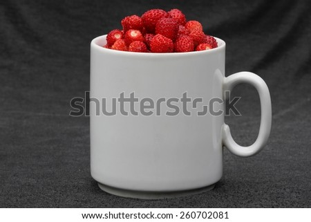White cup with wild strawberries - stock photo