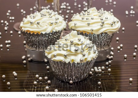 White cupcakes with decorative silver sprinkles on a reflective table - stock photo