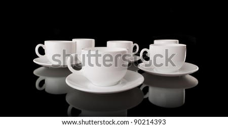 White cups and saucers on a black background - stock photo