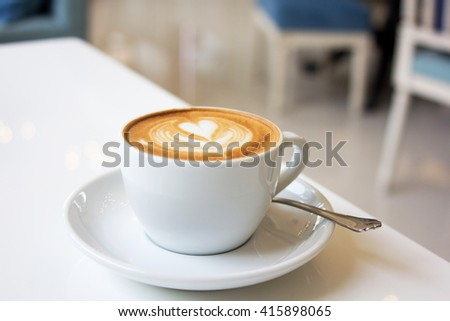 white cups of Cappuccino coffee with froth heart shaped on table - stock photo
