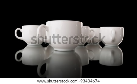White cups on a black background - stock photo