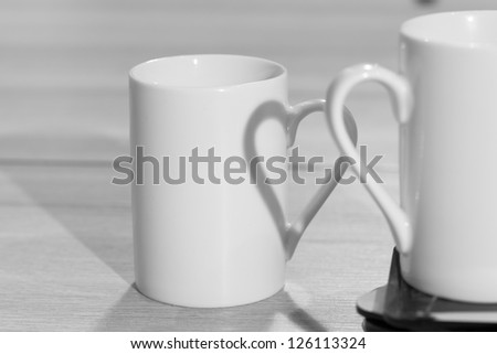 White cups on table with heart shadow