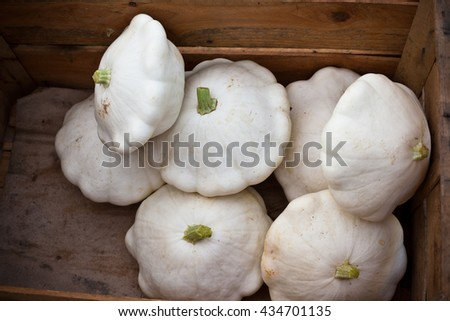 White custard marrows in a wooden box on a farm market - stock photo