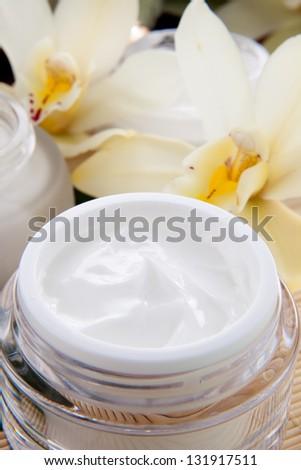 White Cymbidium orchid flower and jar of moisturizing face cream for spa treatment. - stock photo