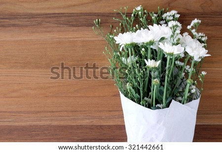 White daisy bouquet on wood background, with copy space