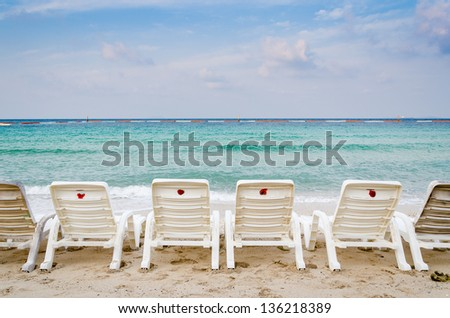 white deck chairs on the beach, sunrise time - stock photo