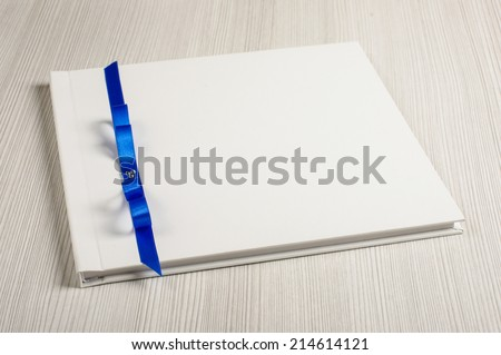 White decorated wedding guest book on the bright table - stock photo