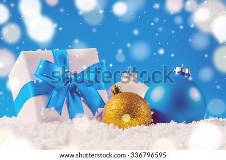 white decorative christmas gift box with ribbon and balls on snow against blue festive background