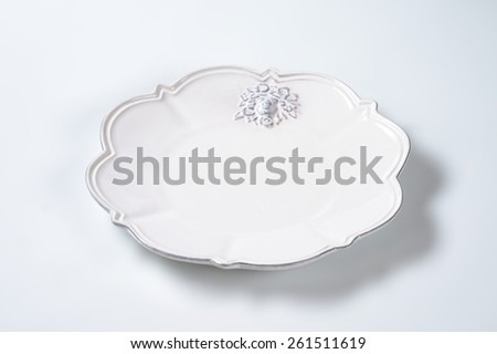 white decorative plate on white background - stock photo
