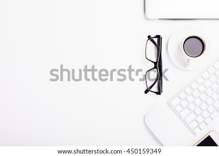 White desktop with glasses, coffee cup, smartphone computer mouse, keyboard and other items. Top view, Mock up - stock photo