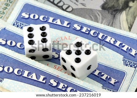 White Dice Laying on Social Security Card - Gambling on benefits and retirement income - stock photo