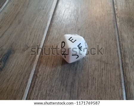 white dice with many sides with letters and brown wooden floor