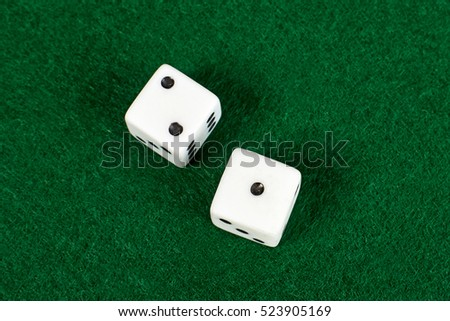 White dices on green table.