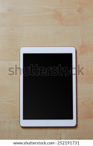 White digital tablet on a wooden desk with blank screen, space for text, top view - stock photo