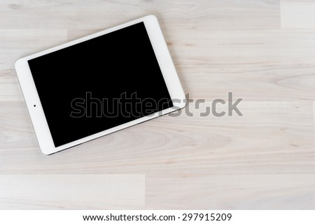 White digital tablet on bright wooden table - stock photo