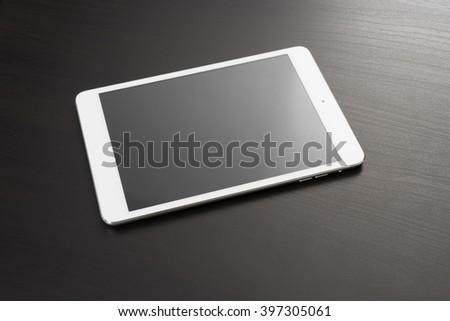 White digital tablet on dark wooden table - stock photo