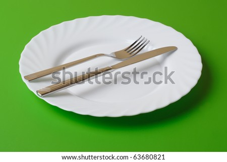 White dinner plate, knife, and fork on a green background