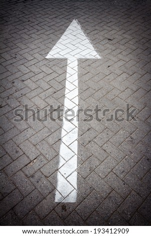 White directional arrow sign on a road - stock photo