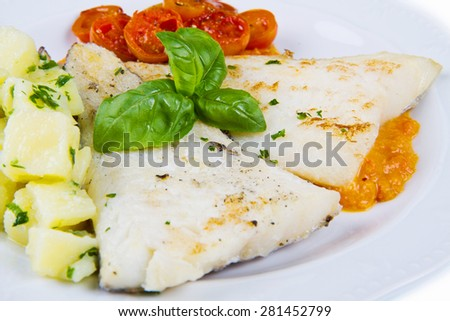 white dish of Fresh black cod with potatoes and tomatoes sauce - stock photo