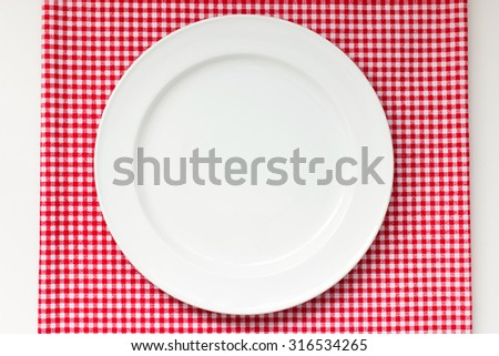 white dish or plate on red classic checkered tablecloth texture on white table with copy space for advertise food product and other