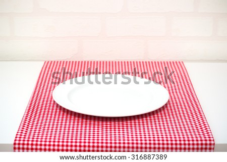 white dish or plate on red classic checkered tablecloth texture on white table with copy space for advertise food product and other - stock photo