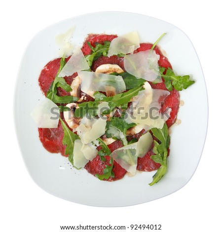 white dish with carpaccio of beef on arugula over white background. Top view. - stock photo