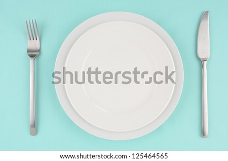 White dishes with knife and fork on aqua tablecloth