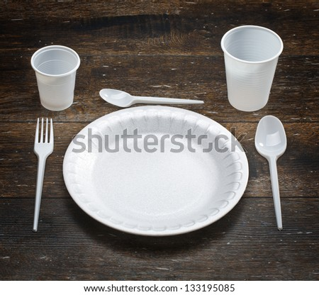 white disposable dishware set in a dark wood - stock photo