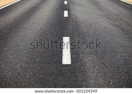 White dividing line on the road surface with the roadside - stock photo
