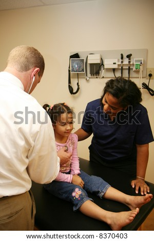 White Doctor and Hispanic nurse check young child - stock photo