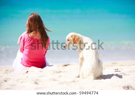 White dog sitting on tropical beach with woman and baby on background - stock photo