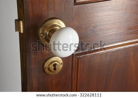 White door knob over a rustic traditional wooden door. Horizontal