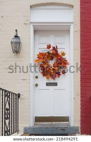 White door with thanksgiving wreath - stock photo