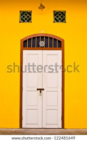 white door with yellow wall - stock photo
