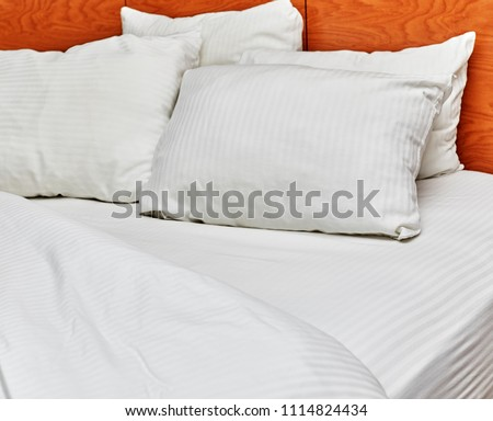 White down pillows leaning against a headboard with white sheets pulled down on a bed