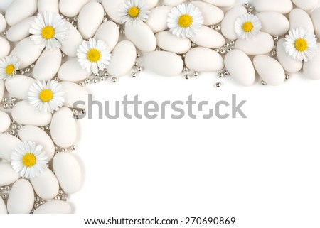 white dragees with silver spheres and daisies on white background - stock photo
