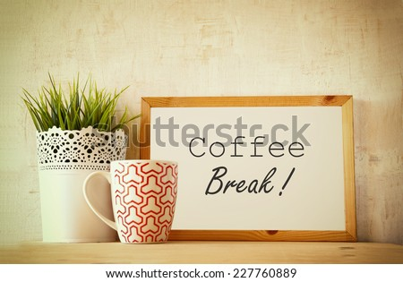 white drawing board with the phrase coffee break over wooden table with coffe cup and flower pot decoration . filtered image - stock photo