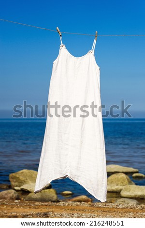 White dress hanging on a rope on the sea background