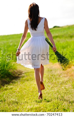 White dress skipping girl in field with flowers at sunset - stock photo