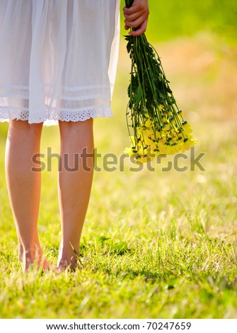 White dress with flowers in hand, spring time concept - stock photo