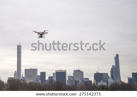 White drone flying in Central Park on a cloudy day - stock photo