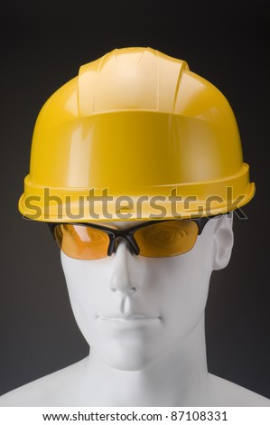 White dummy head with yellow security helmet and glasses